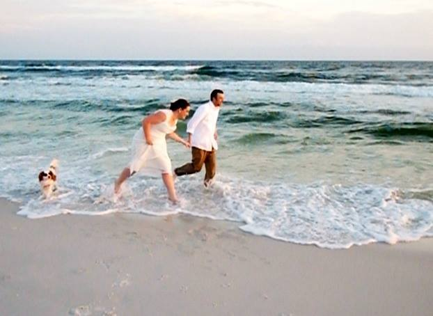 This happy couple and their dog, enjoy a run in the surf after the wedding ceremony.